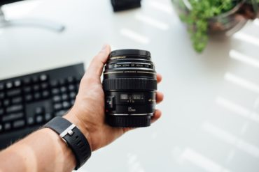Objetivo Nikon sostenido por una mano