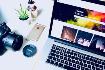 Escritorio con ordenador en la pantalla Unsplash, cámara y iPhone