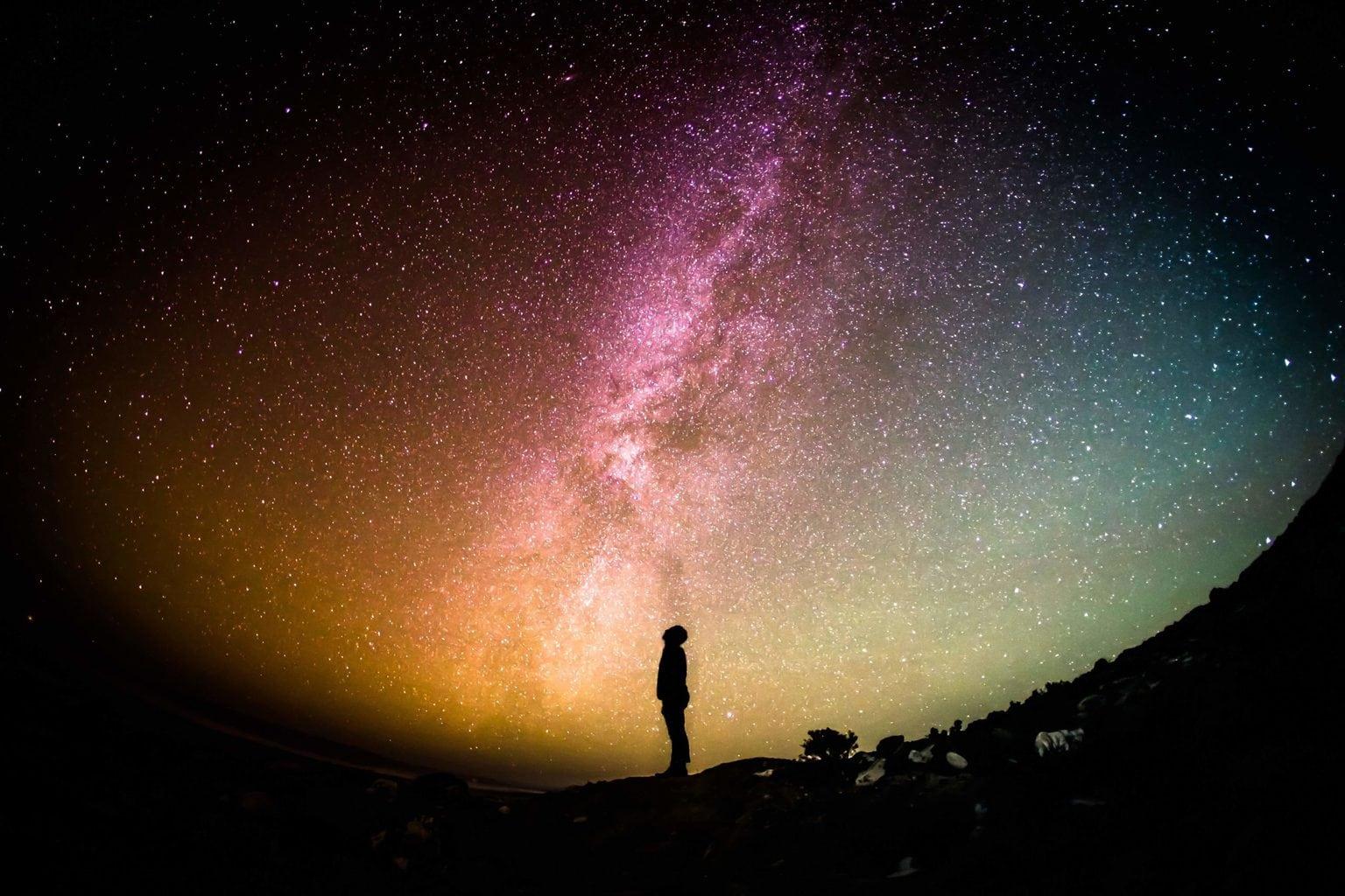 silueta de persona con cielo estrellado de fondo
