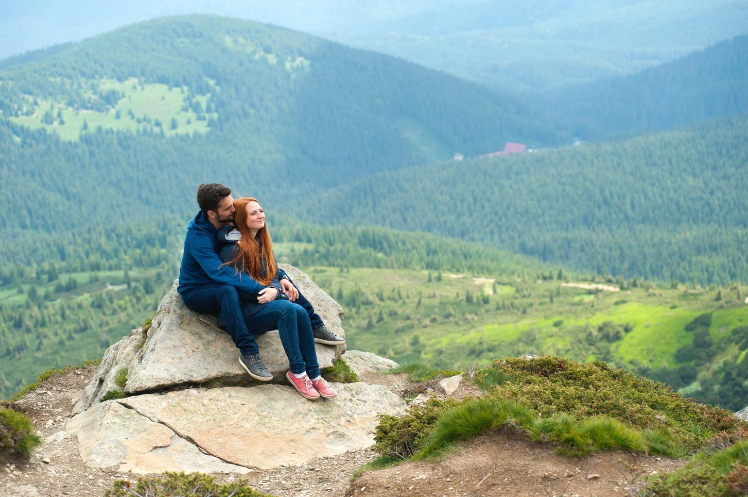 Pareja en lo alto de una montaña con vistas al paisaje