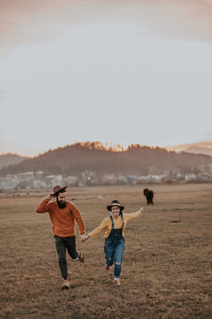 Pareja con sombreros corriendo por el campo
