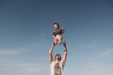 Fotografía de bebé en el aire lanzado por papá