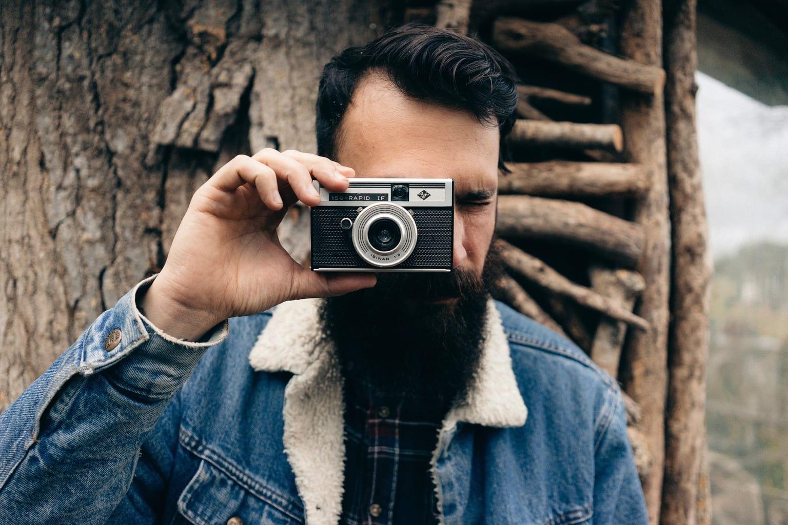 hombre con barba mirándo a través del visor de cámara