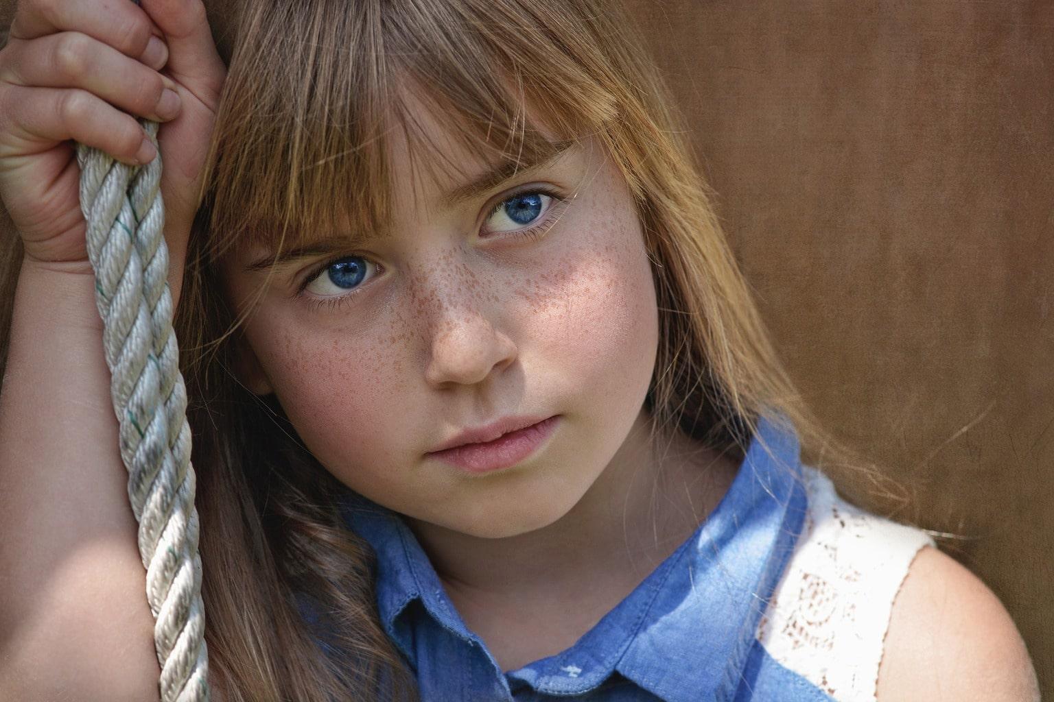 Retrato de niña con pecas y ojos azules