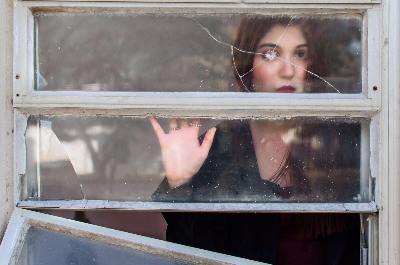 Retrato chica detrás de una ventana