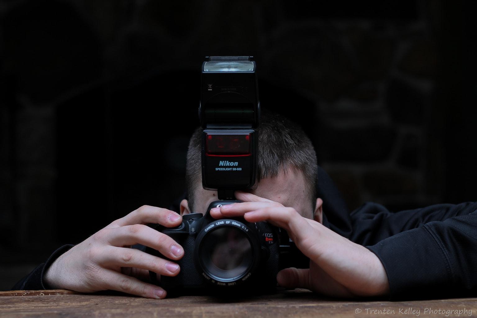 retrato de un hombre con un flash montado en réflex
