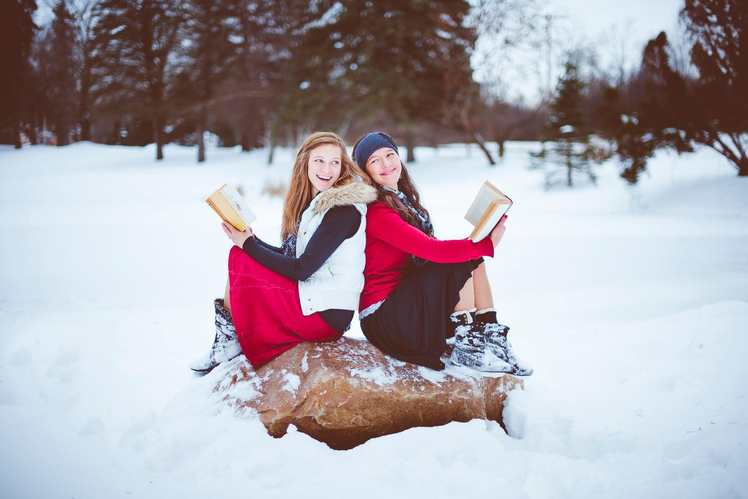 fotografía de dos chicas en la nieve con libros
