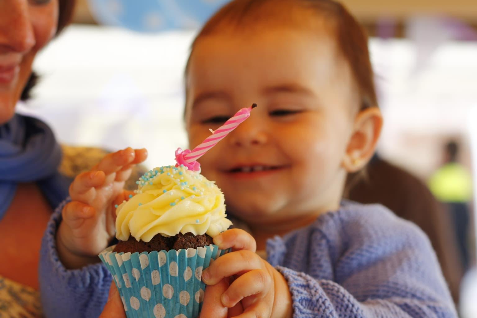 Fotografía de un niño con una cupcake de cumpleaños
