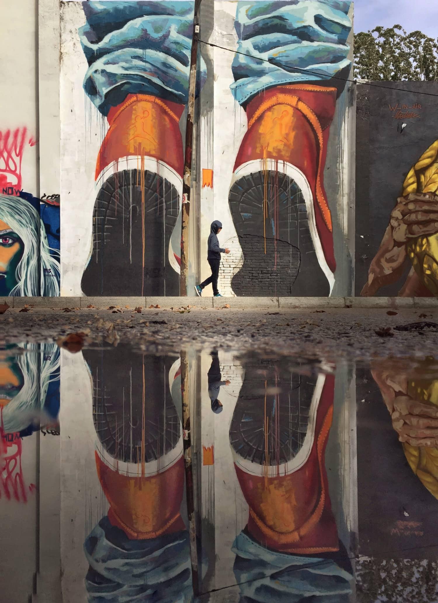 Fotografía callejera de un grafiti reflejado en un charco de agua