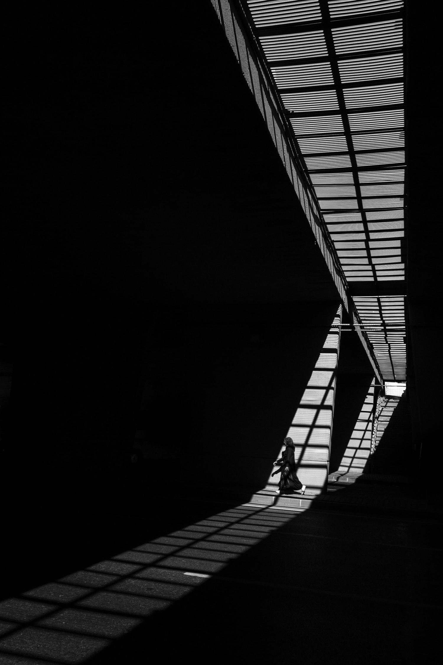 fotografía blanco y negro mujer caminando luz dura