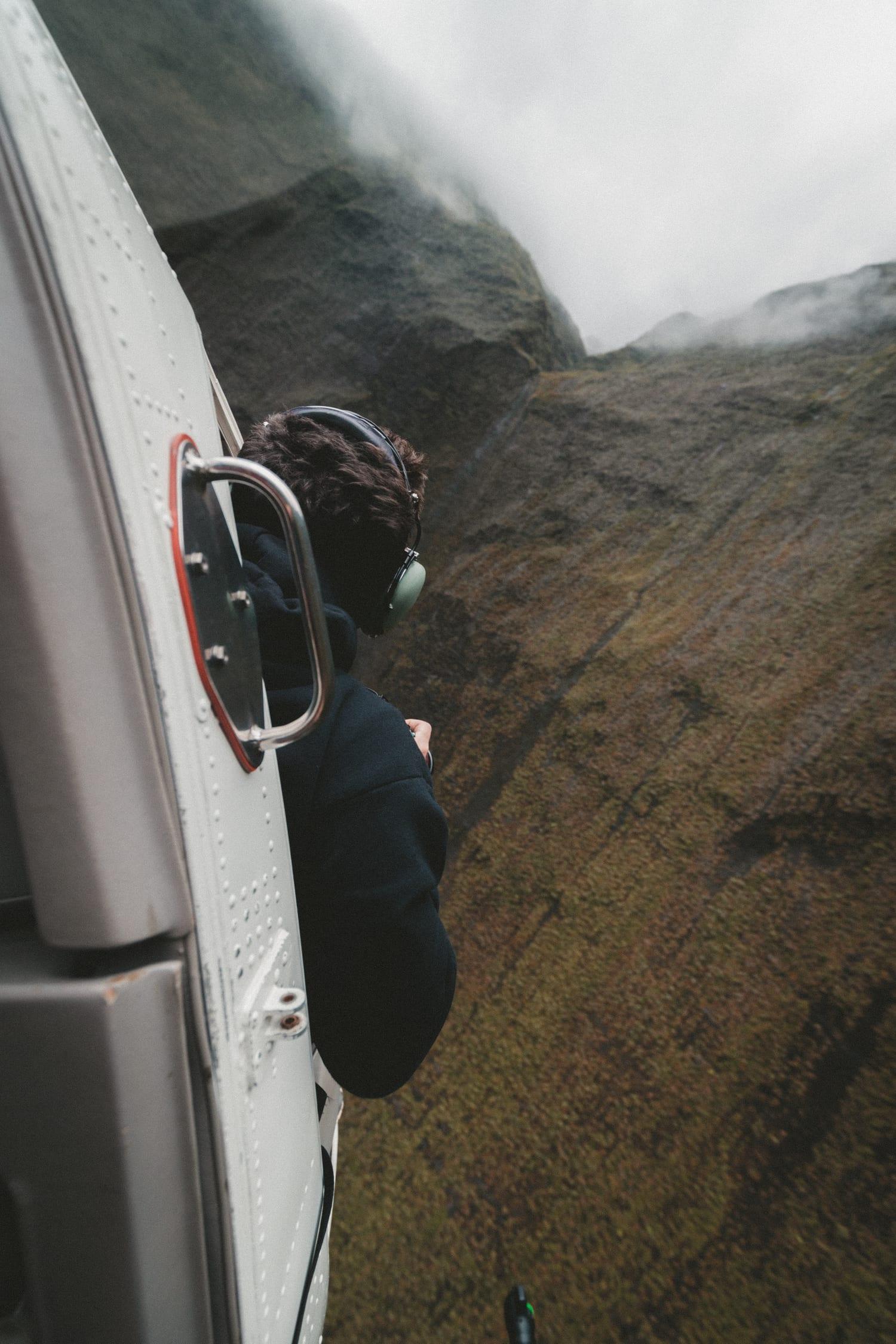 fotografía hombre asomando desde un helicóptero