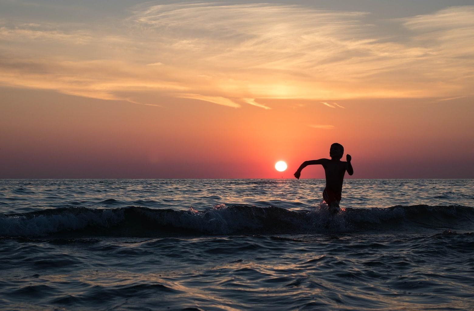 Fotografía atardecer con un niño jugando en la playa