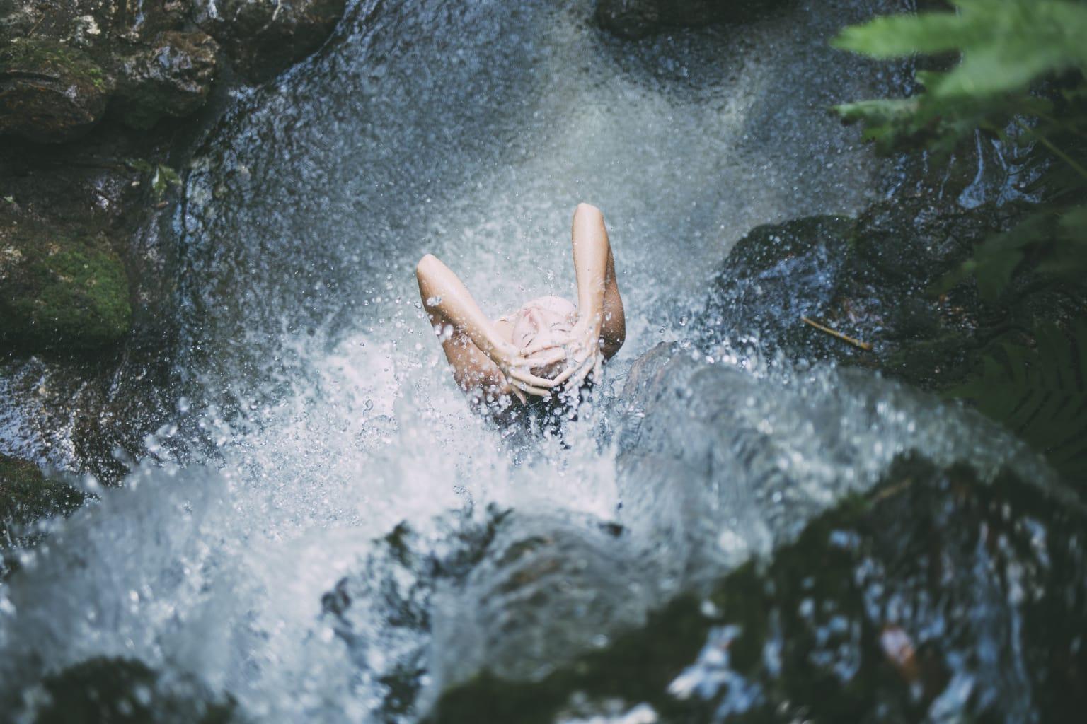Fotografía veraniega de una chica debajo una catarata