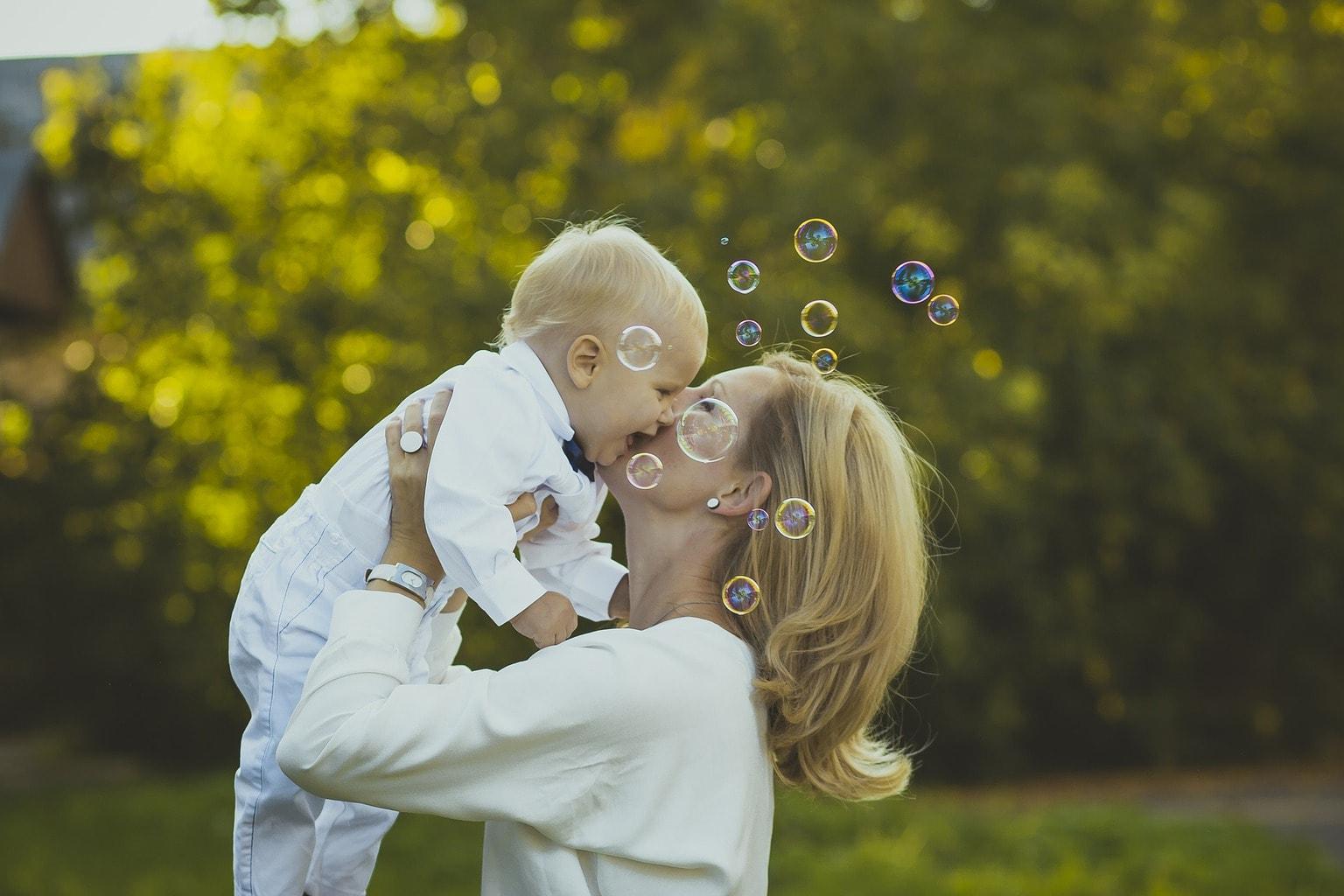 Fotografía de una madre con bebé y burbujas