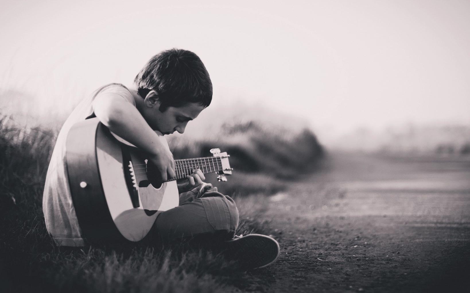 fotografía un niño tocando la guitarra