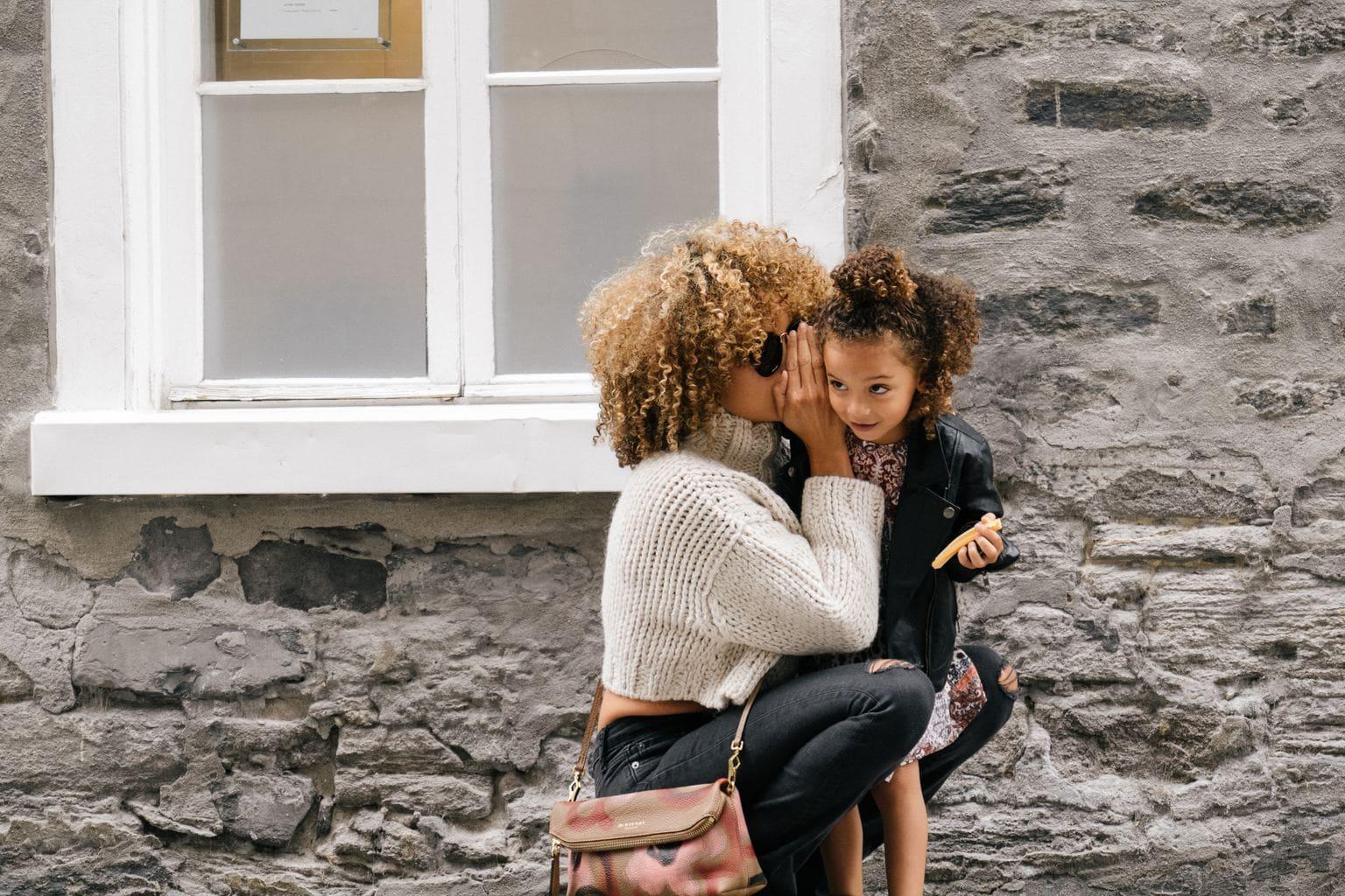 fotografía una madre susurrando a su hija