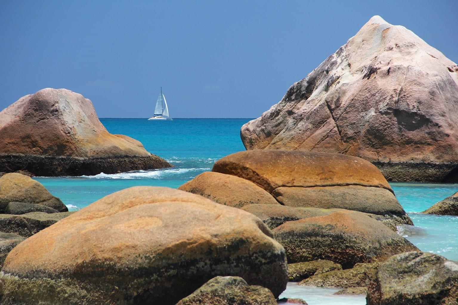 fotografía de rocas y un barco en el mar