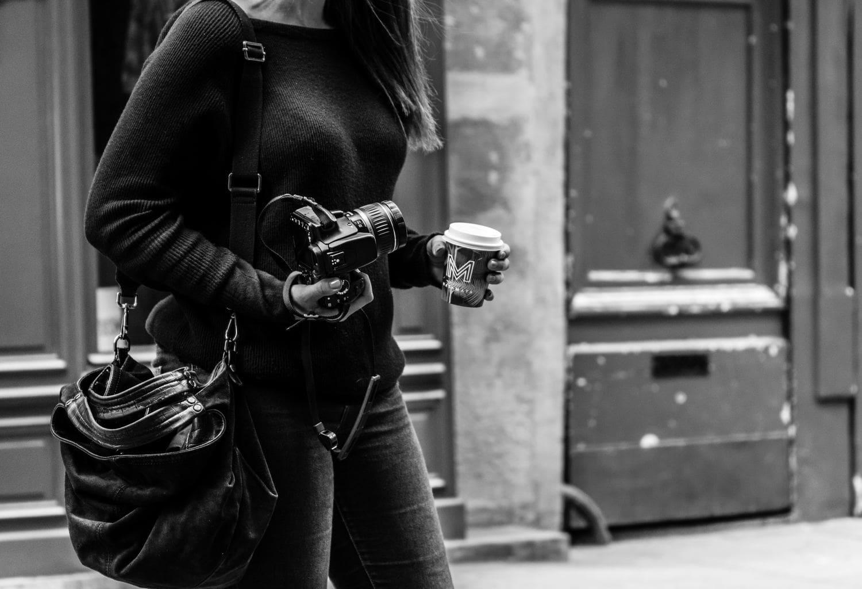 Retrato mujer sujetando una cámara rélfex y café