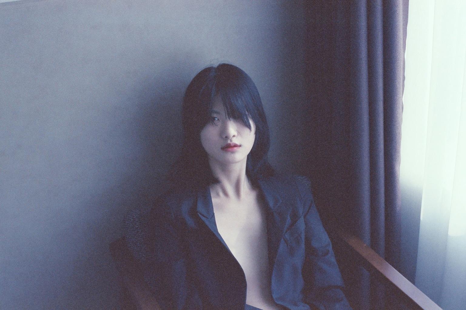 retrato de una mujer al lado de una ventana