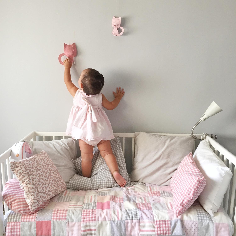 Foto de niña alcanzando un adorno de la pared con luz difusa