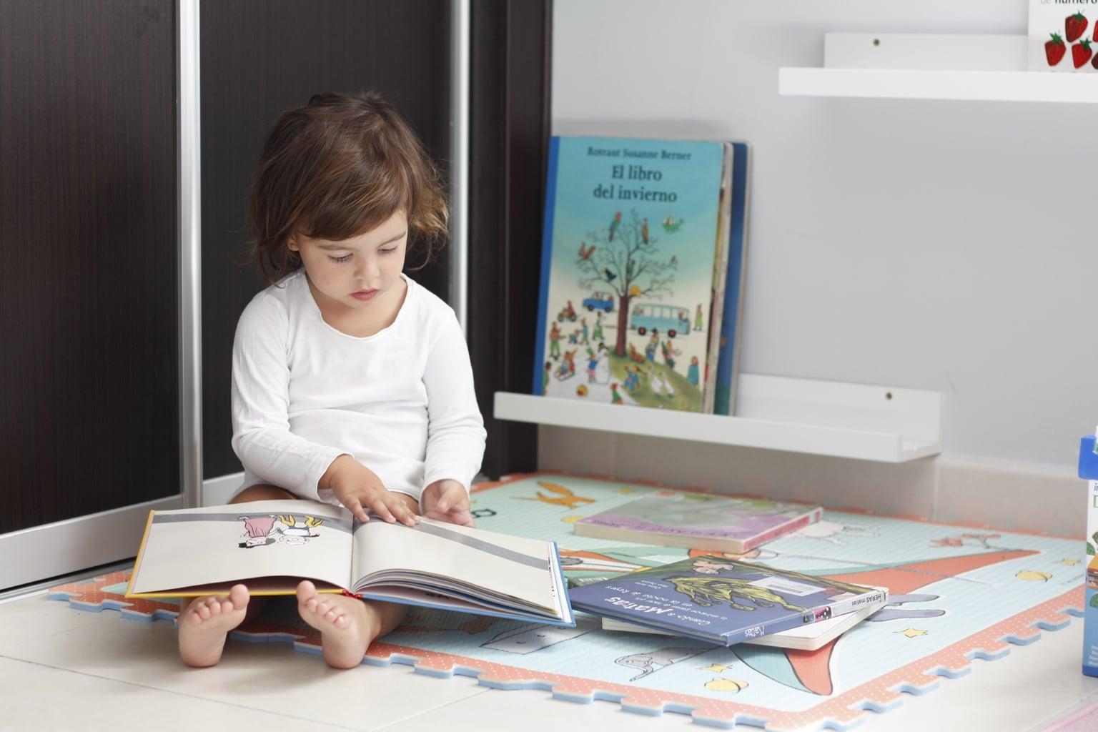 Foto de niña sentada en el suelo leyendo cuentos