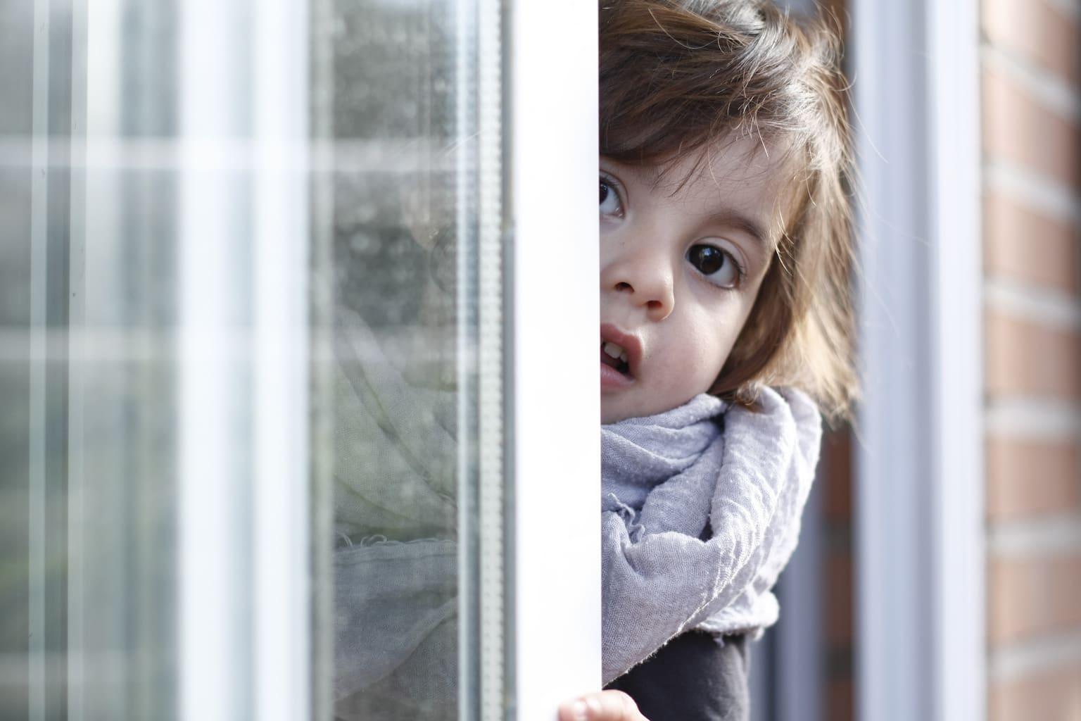 Foto de niña asomándose por una ventana