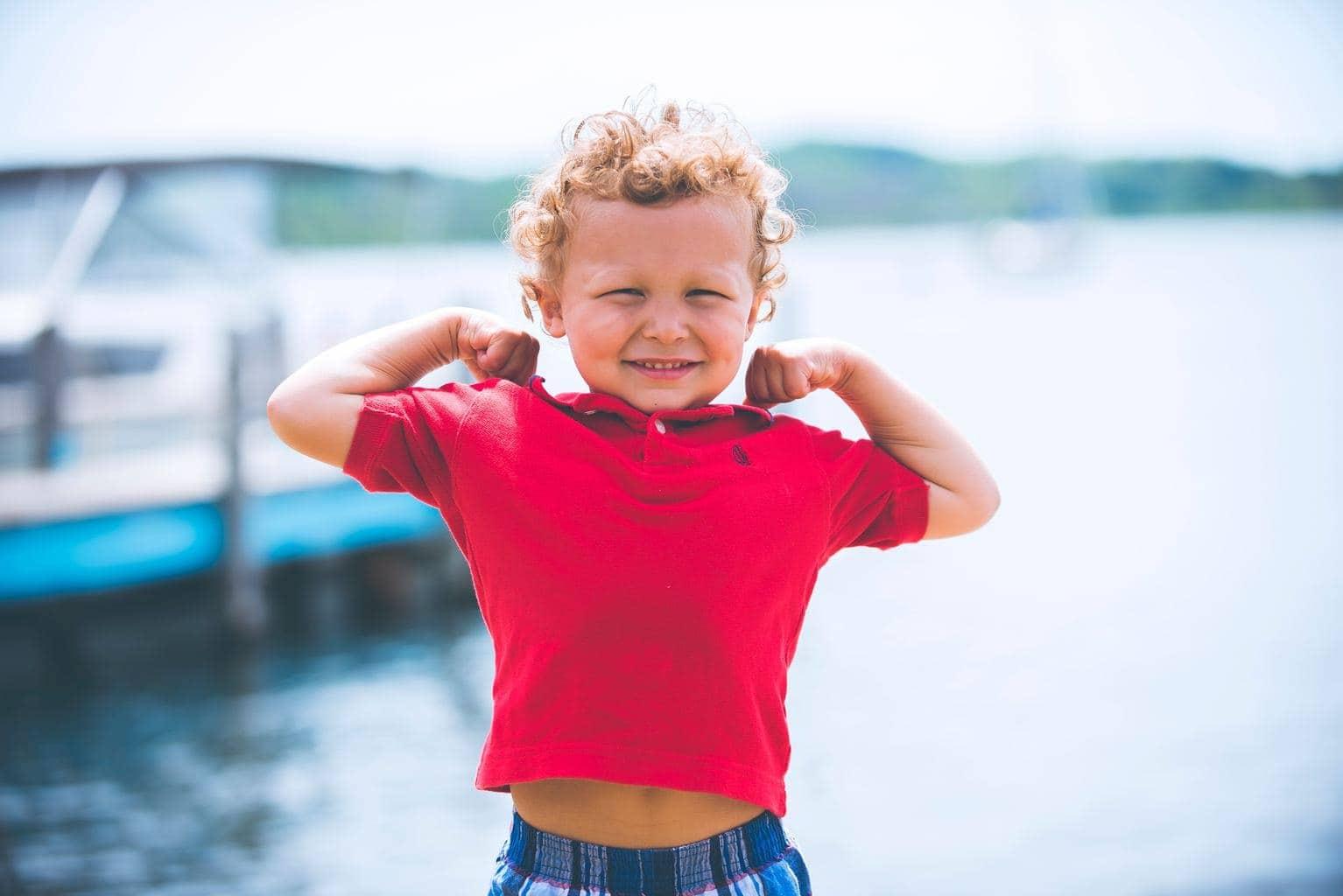 foto de niño con agua al fondo y camiseta roja