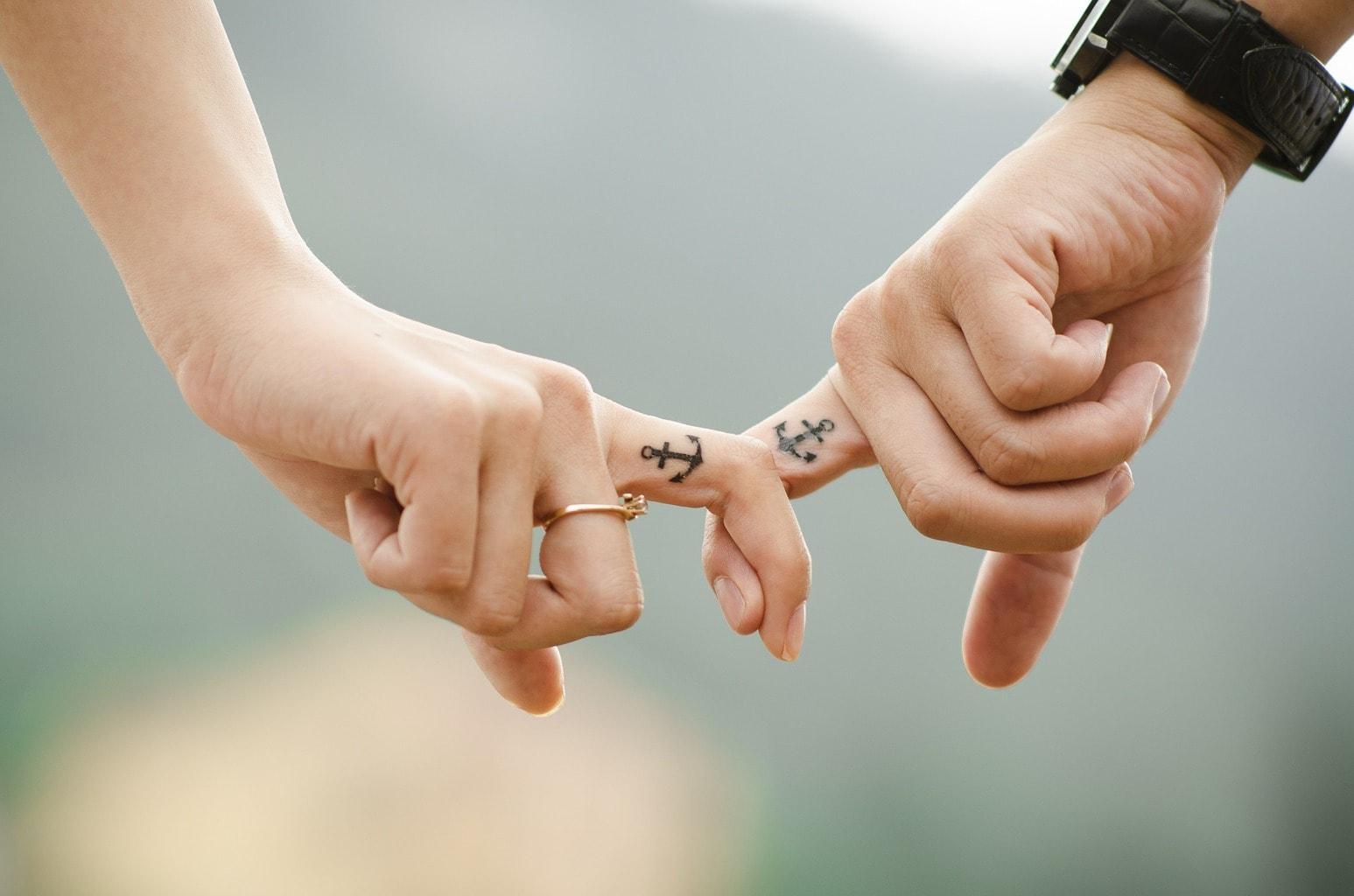 fotografía de pareja con los dedos entrelazados