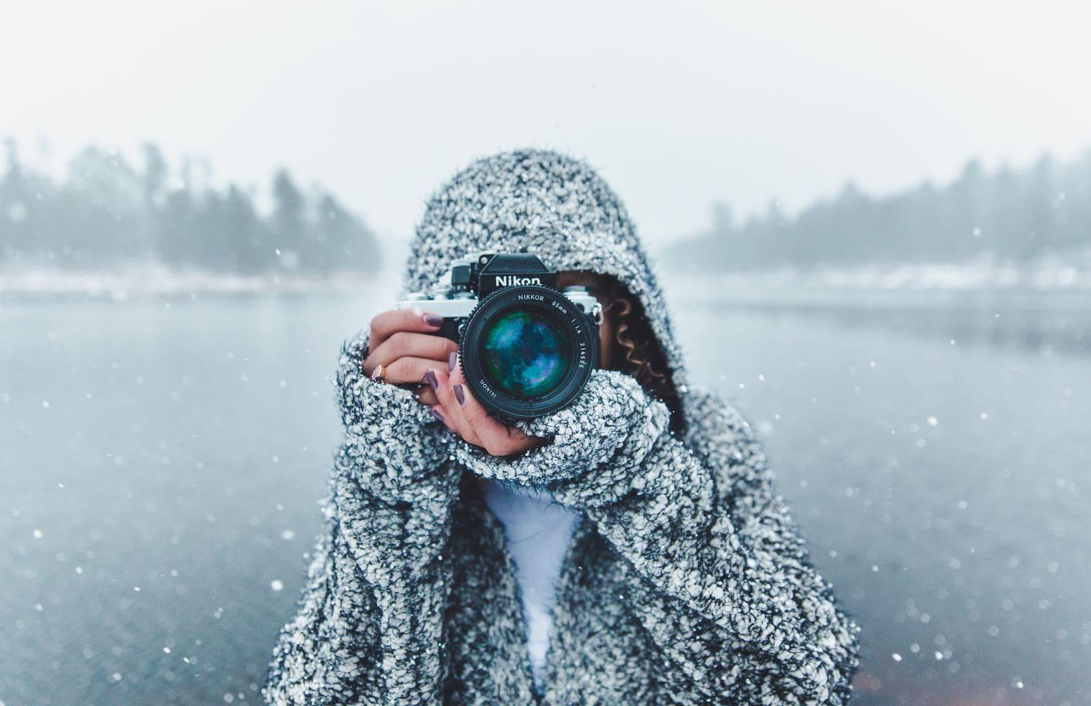 retrato de una mujer con cámara en un paisaje de nieve