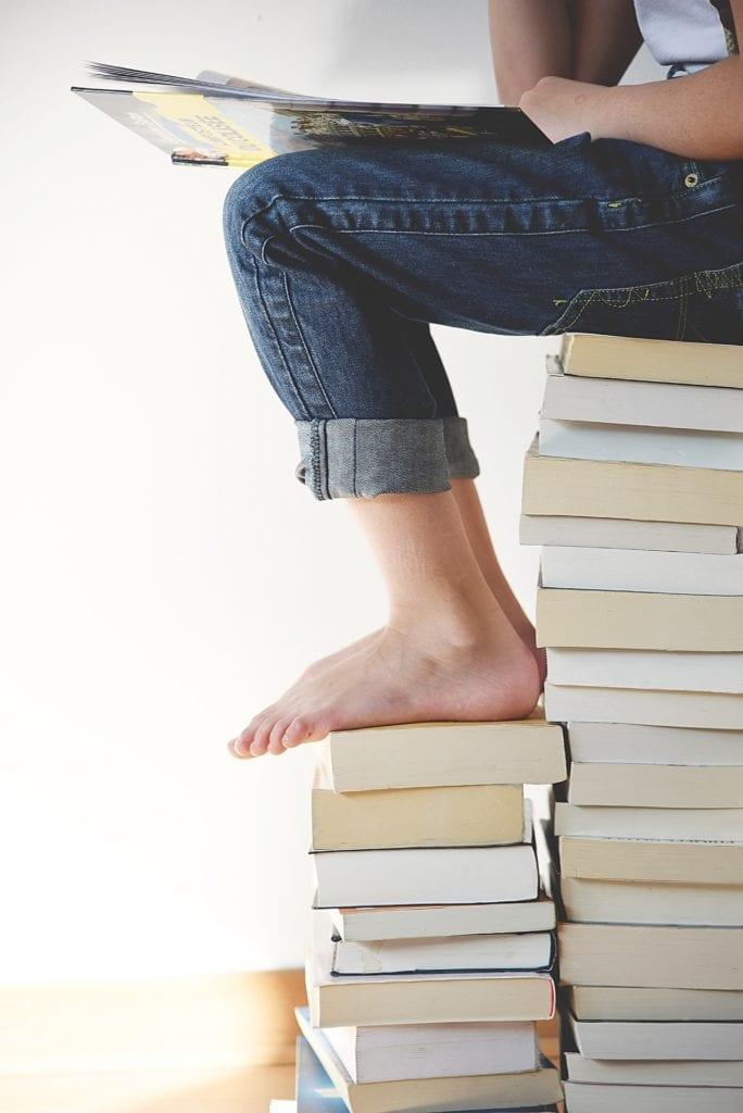 montaña de libros y piernas de alguien leyendo