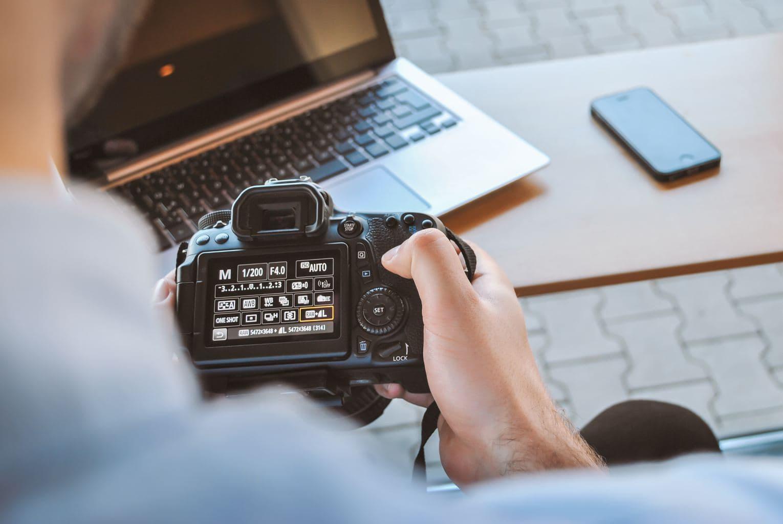 fotografía de un hombre sujetando una cámara réflex