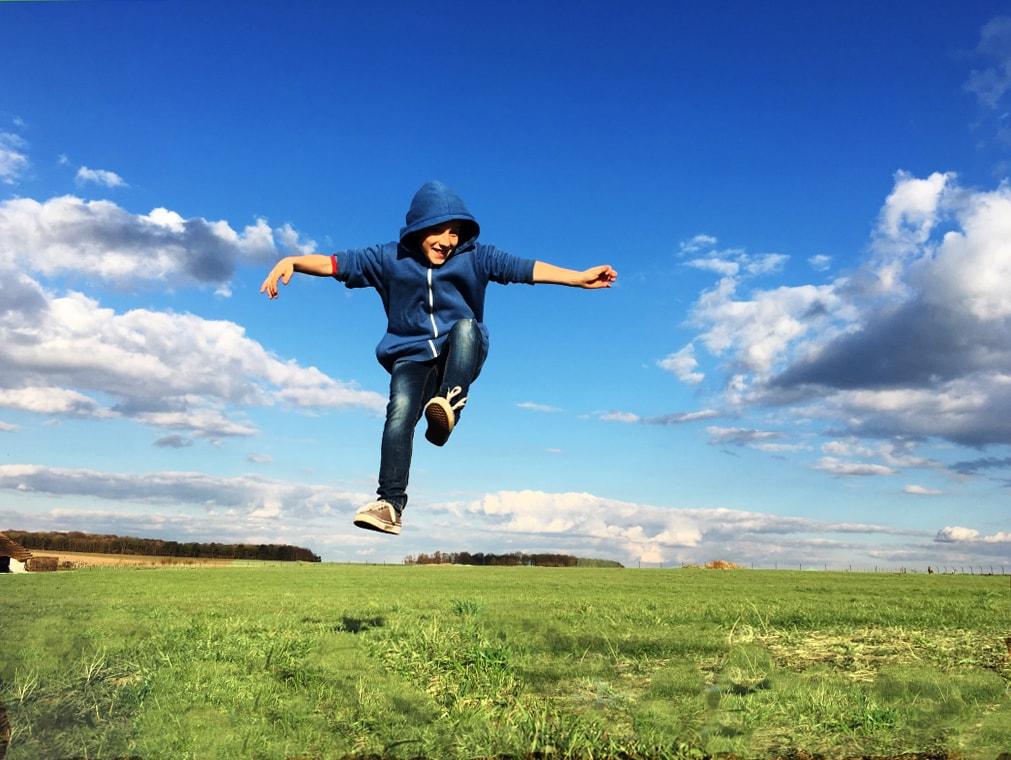 un niño saltando en un campo