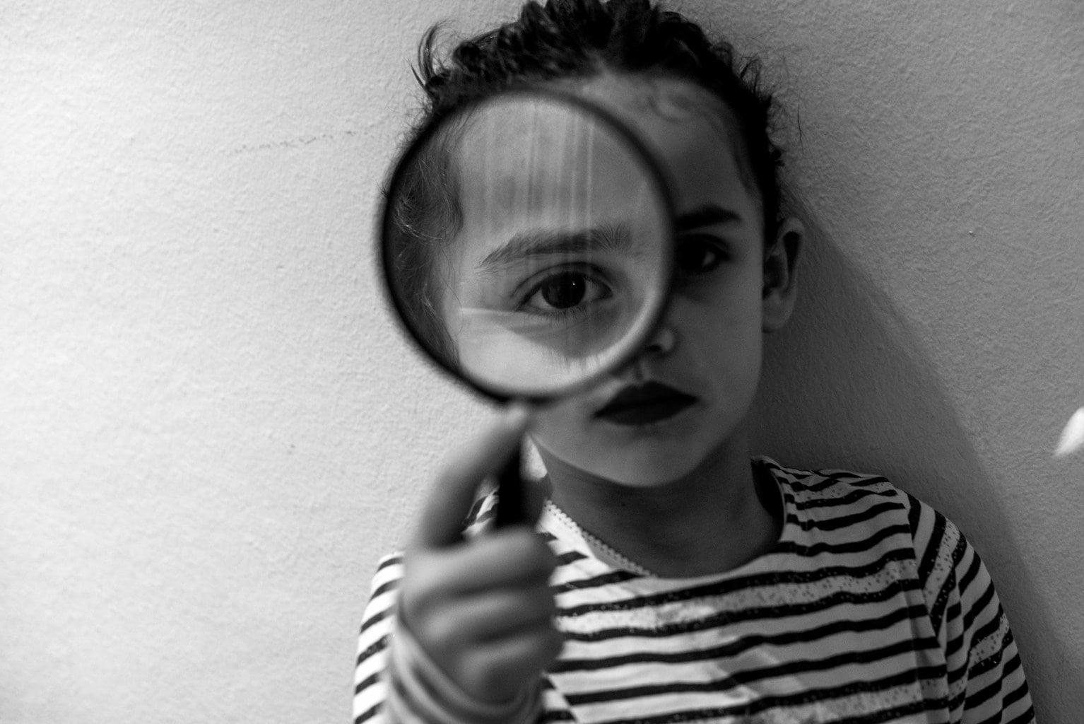 retrato de una niña con una lupa