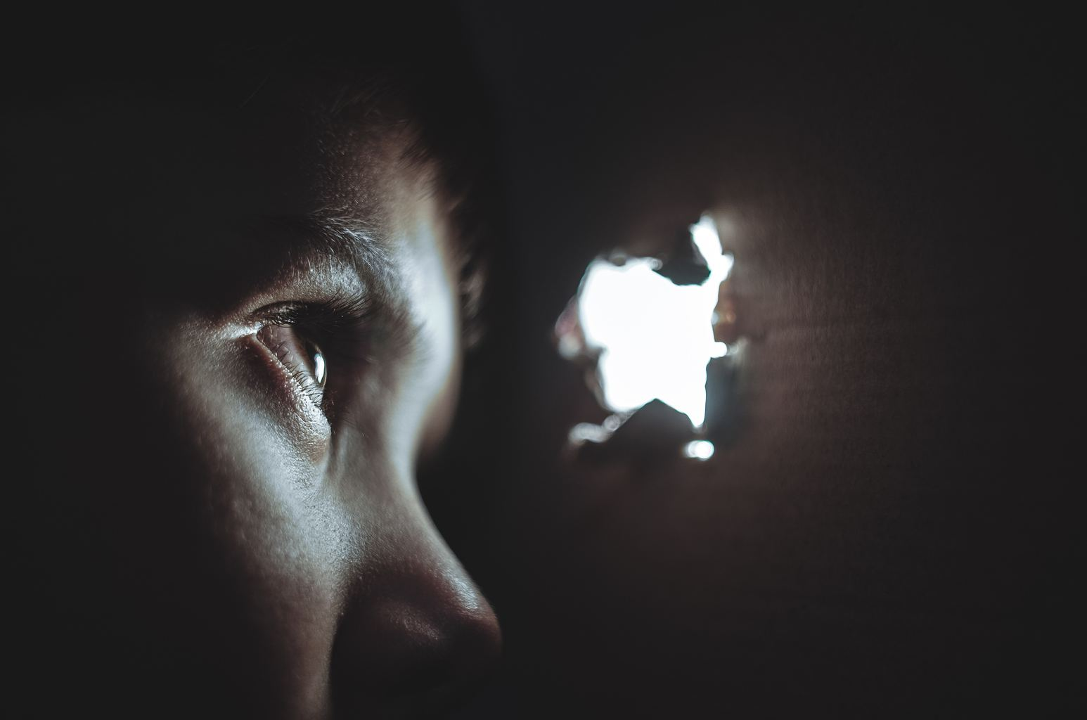 retrato de un niño mirando por un agujero
