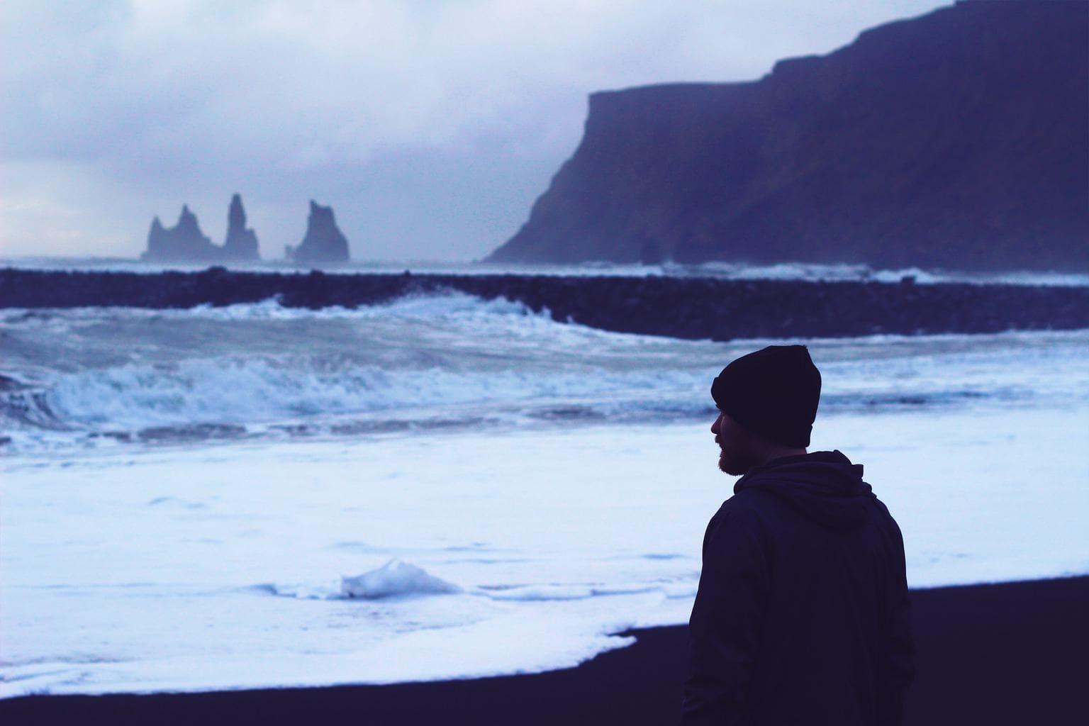 fotografía fría de un hombre mirando las olas