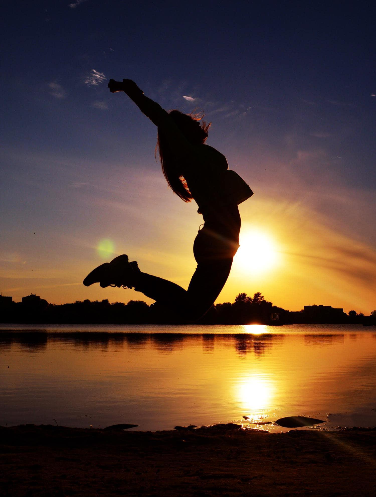 Fotografía de una chica saltando atardecer