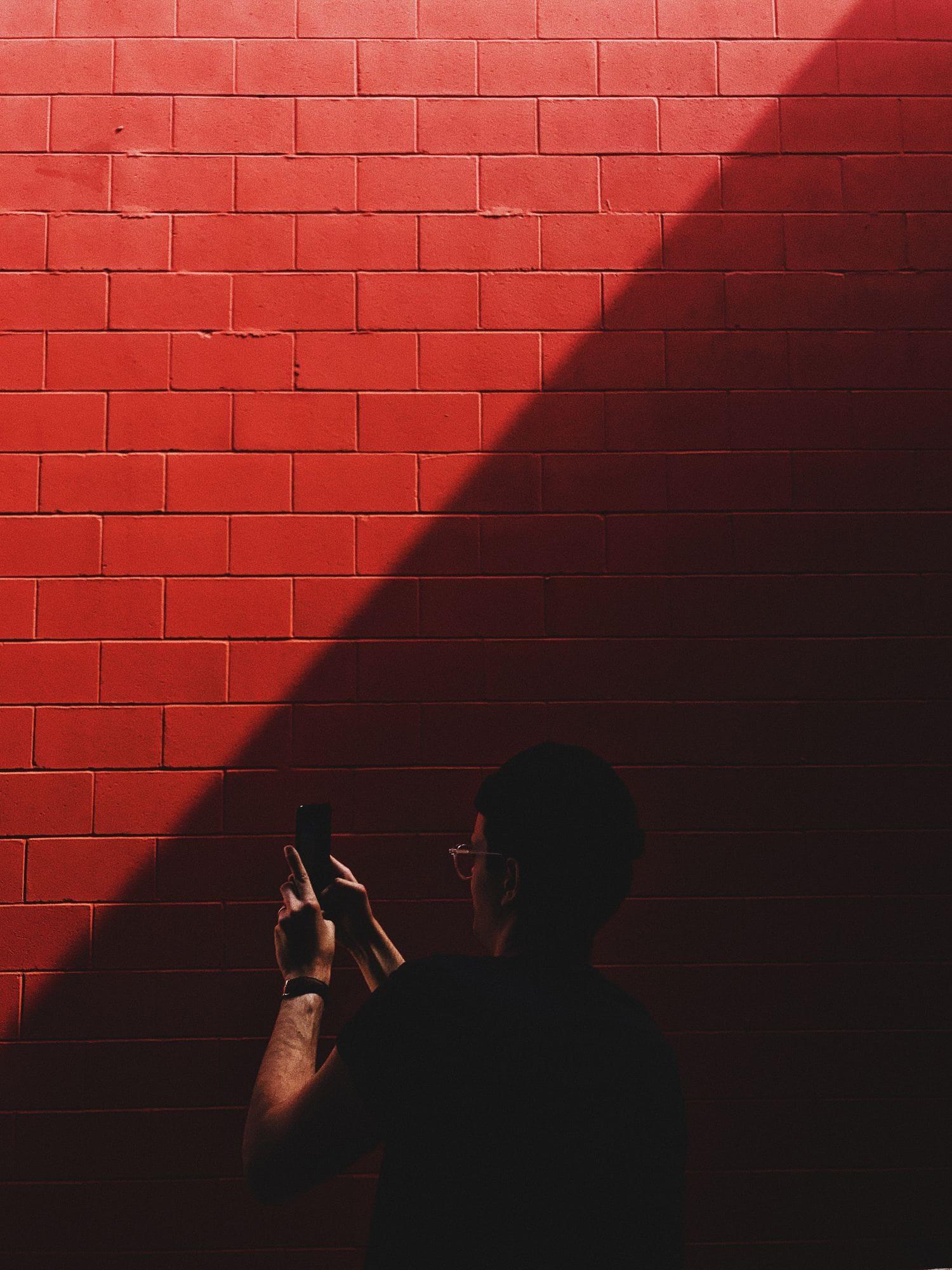 fotografía móvil hombre muro rojo