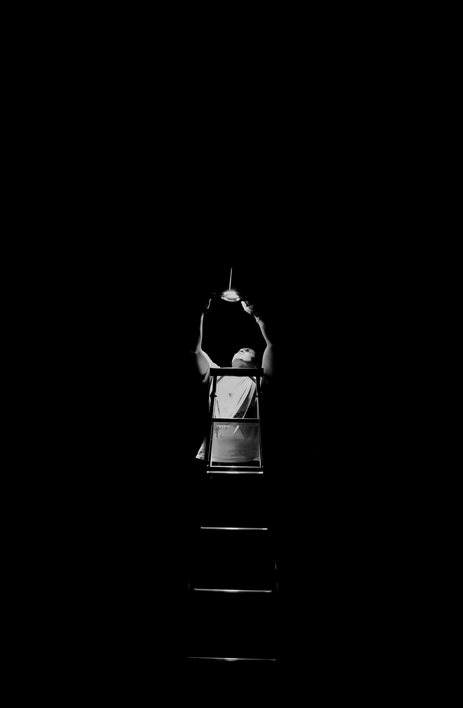 fotografía hombre arreglando luz clave baja
