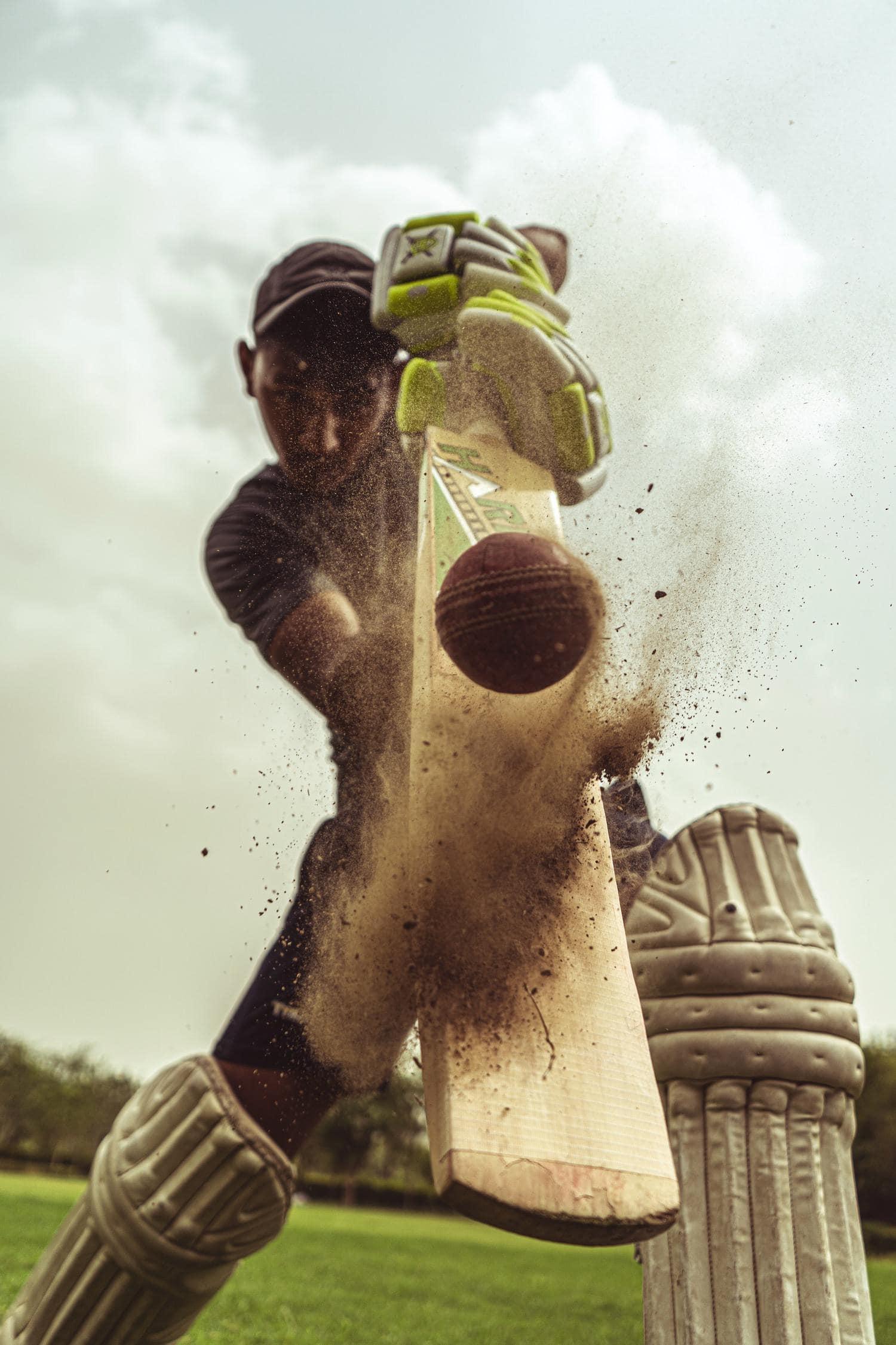 Jugador de cricket golpeando bola