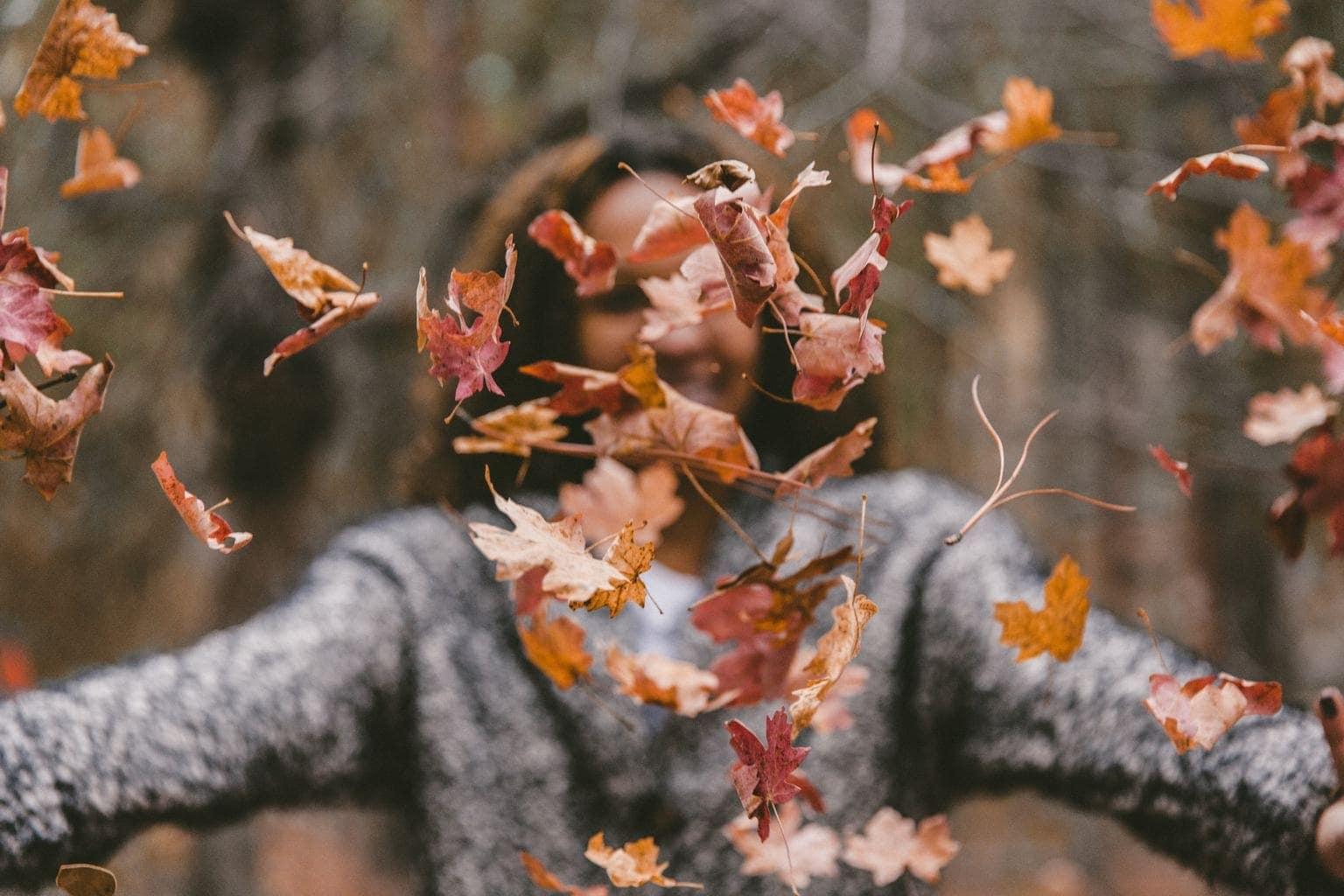 fotografía de una chica jugando con hojas