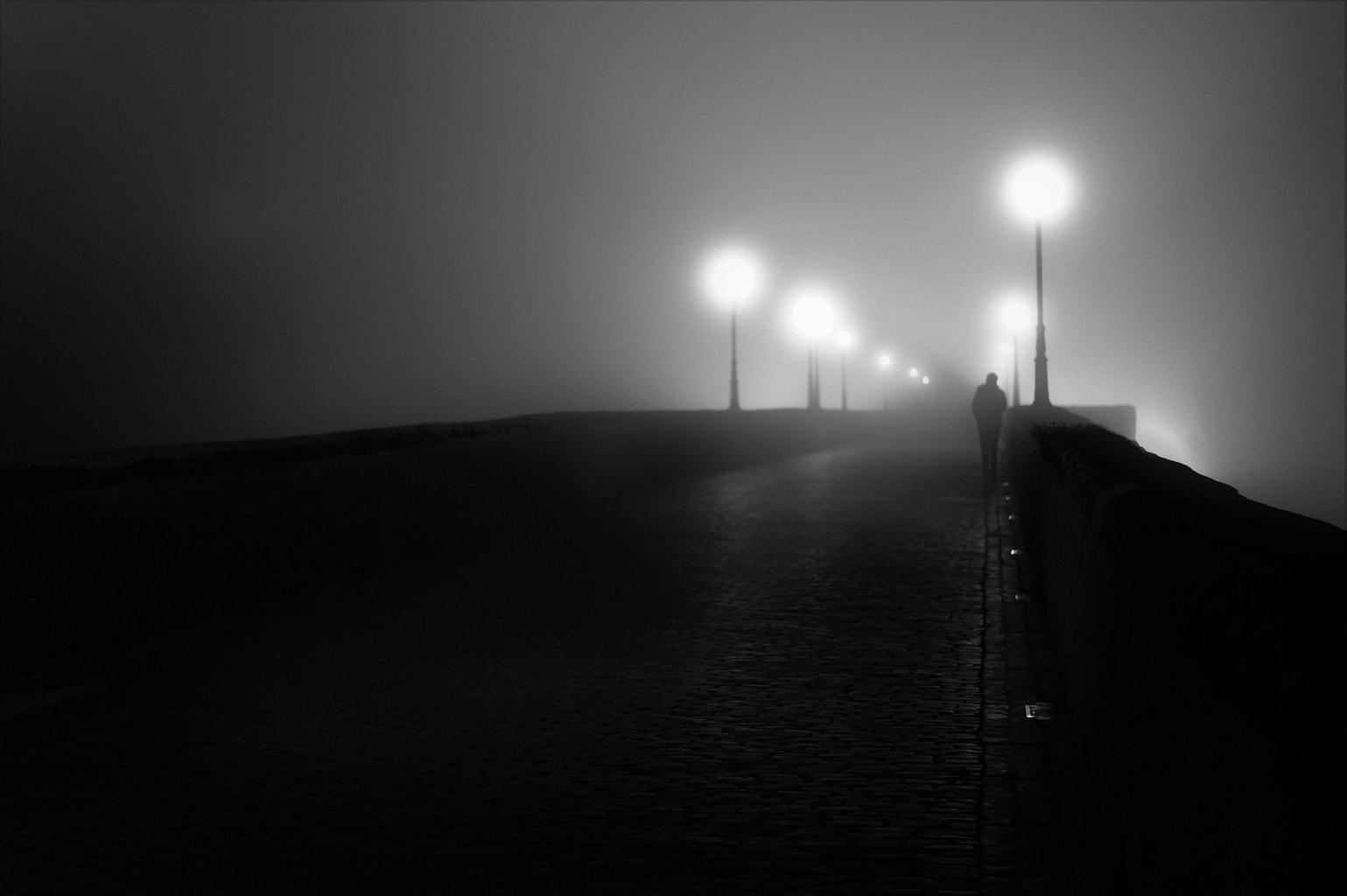 un hombre cruzando un puente entre la niebla