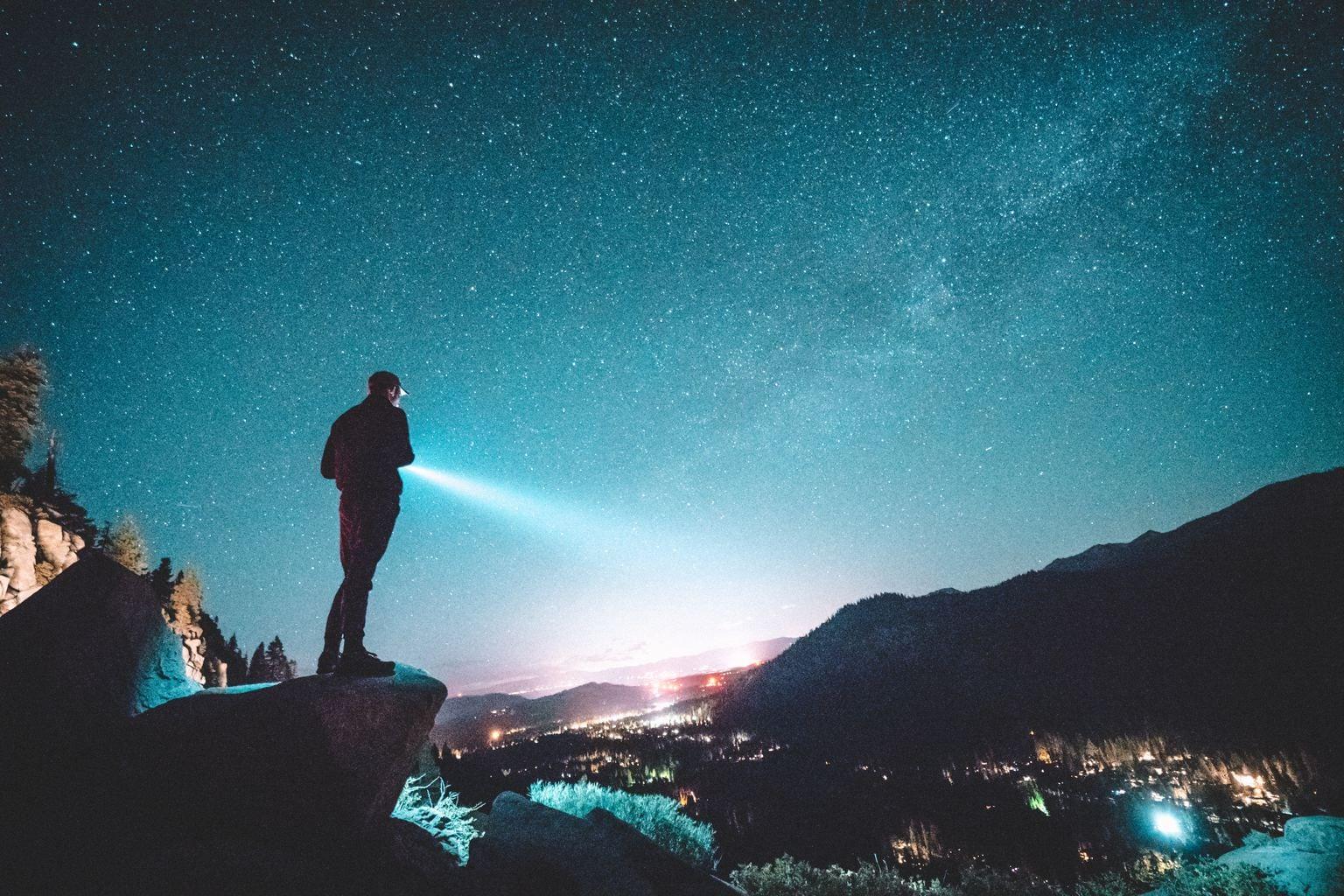 hombre linterna cielo noche