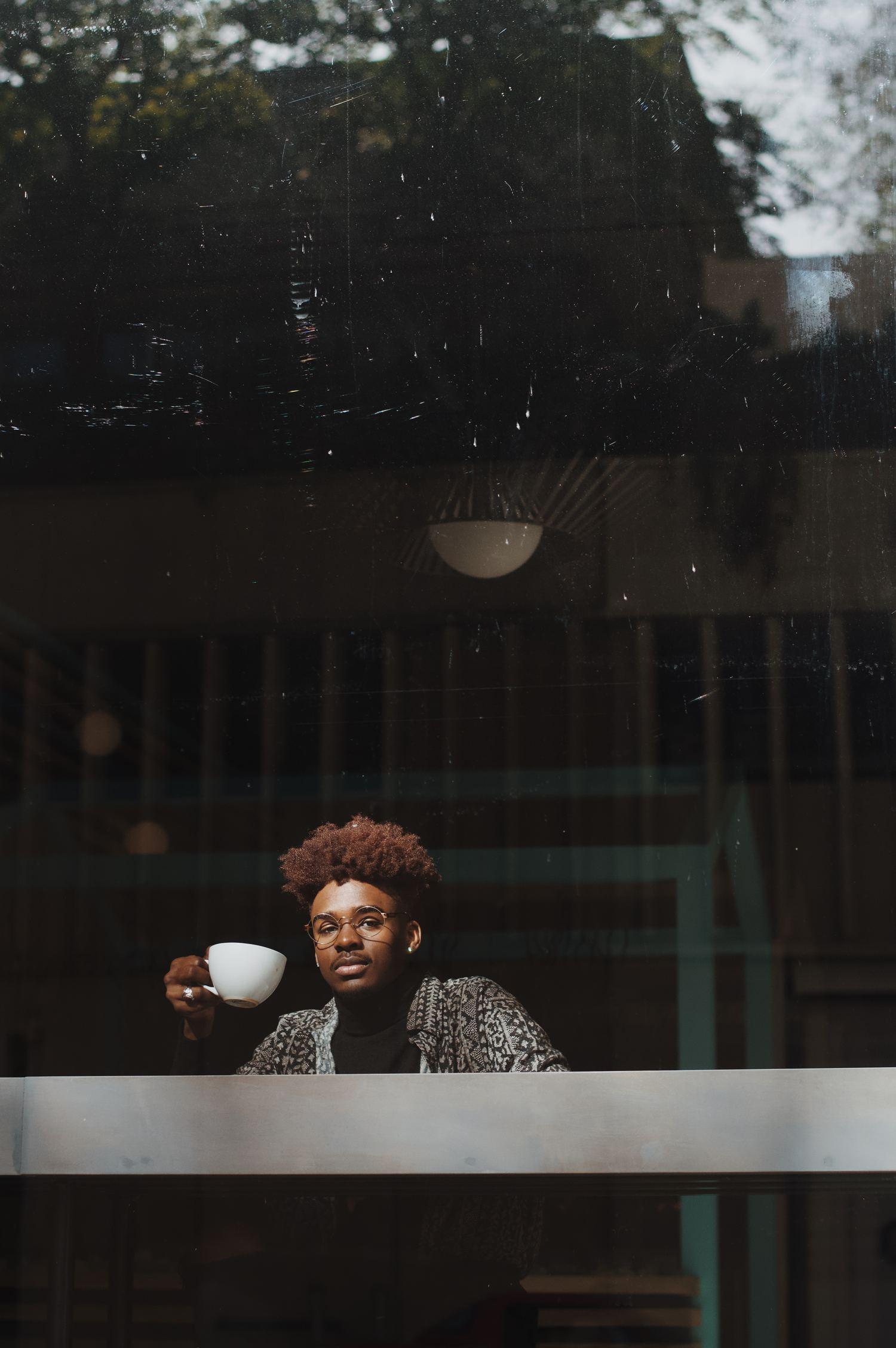 Joven pelo afro tomando café a través de un cristal