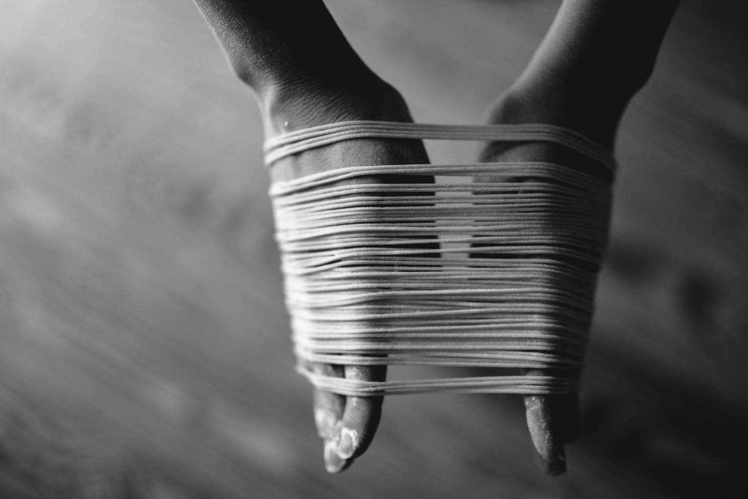 manos enredadas en hilo