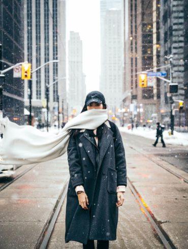 Mujer con bufanda en medio de la calle nevando