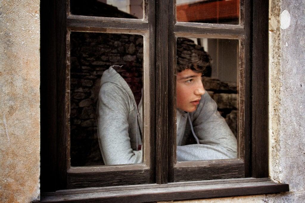Joven asomado a una ventana