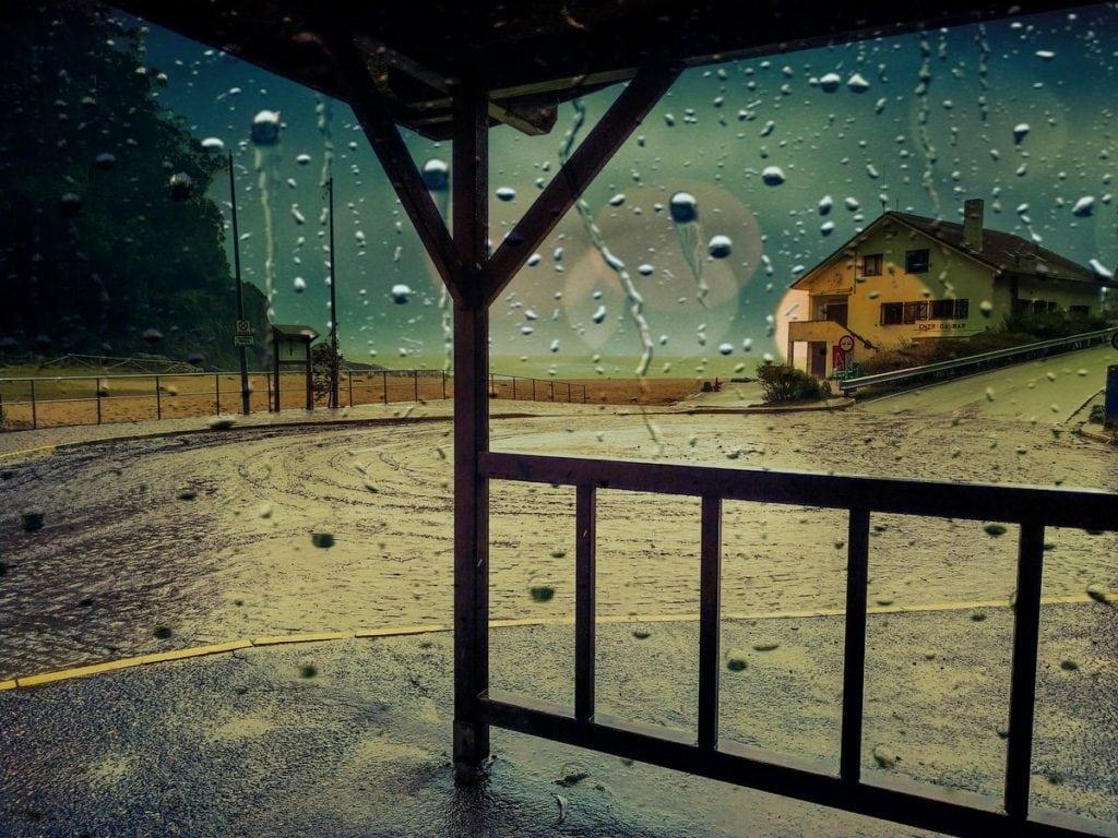 Una casa detrás de un cristal mojado