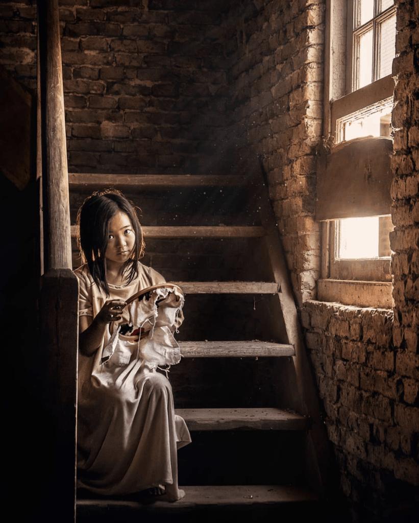 niña bordando bajo luz ventana