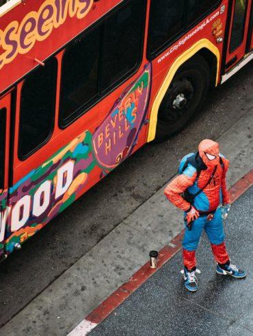 Hombre disfrazado de Spiderman al lado de un bus
