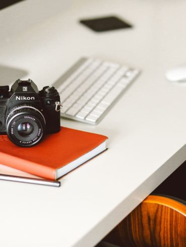 Cámara Nikon sobre agenda roja en un escritorio